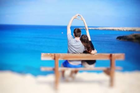 Фото Парень и девушка сидят на скамейке у моря, сложив пальцы рук в виде сердечка, автор Ксения Коновалова