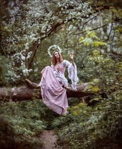 Фото Девушка в розовом платье сидит на поваленном стволе дерева, над ее головой в виде нимба расположен венок из белых цветов, фотограф Ирина Джуль, модель Светлана Марусик