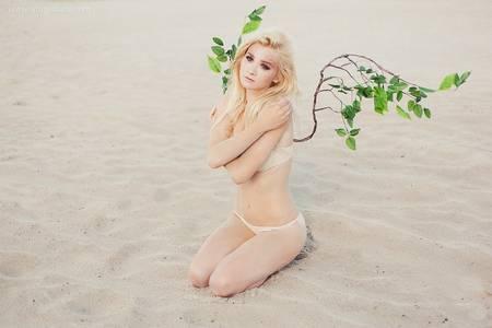 Фото Грустная блондинка сидит на песке, за ее спиной видны крылья в виде цветущих веток дерева, фотограф Диана Латуга