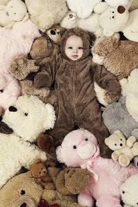 Фото Ребенок в комбинизончике среди мягких игрушек