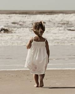 Фото Маленькая девочка в белом сарафане идет к морю