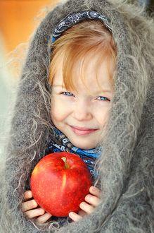Фото Рыжеволосая, голубоглазая девочка с милой улыбкой, в теплом платке и с красным яблоком в руках, фотограф Романова Алена