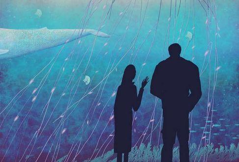 Фото Мужчина и женщина в полумраке смотрят на проплывающих мимо китов