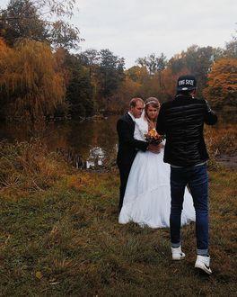 Фото Фотограф фотографирует молодоженов у озера