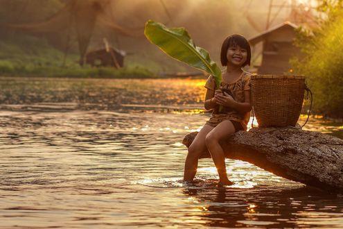 Фото Девочка, улыбаясь, сидит на бревне, держа в руках большой лист