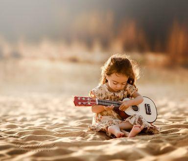 Фото Маленькая девочка сидит на песчанном пляже, держа в руках гитару