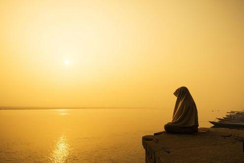 Фото Человек укрыв голову тряпицей, сидит у края обрыва, глядя вдаль