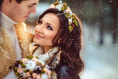 Фото Девушка с венком из цветов на голове и с букетом цветов в руках стоит рядом с парнем и смотрит на него с обожанием, за ними виден падающий снег, фотограф Елена Смирнова