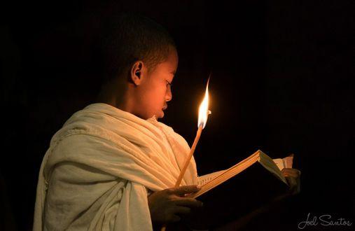 Фото Мальчик, монах стоит в полумраке со свечой и книгой в руках, фотограф Joel Santos