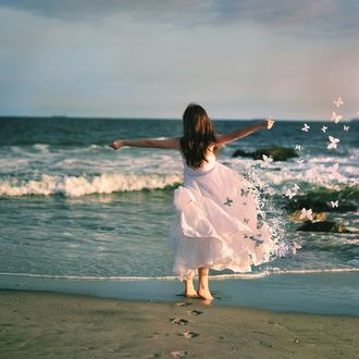 Фото Девочка стоит у воды в платье, которое превращается в разлетающихся бабочек