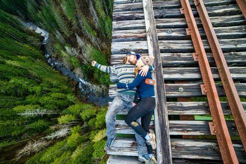 Фото Парень с девушкой лежат в обнимку на краю деревянной кромки железной дороги, проведенной высоко над рекой