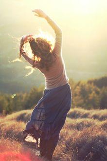 Фото Кудрявая девушка, в поле, стоит лицом к яркому солнцу