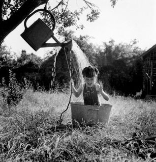 Фото Девочка сидит в большом тазу и поливает себя водой с лейки, подвешенной к дереву, фотограф Robert Doisneau