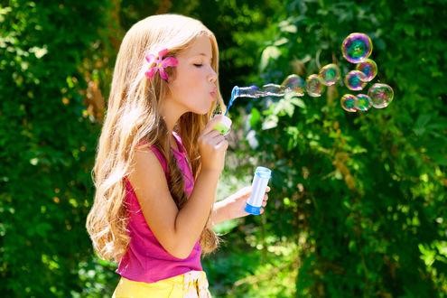 Фото Девочка с цветком в волосах, надувает мыльные пузыри