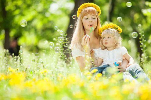 Фото Мама и дочка в веночках из желтых одуванчиков сидят в поле одуванчиков и пускают мыльные пузыри