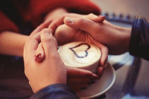Фото Девушка держит чашку каппучино, парень держит ее руки
