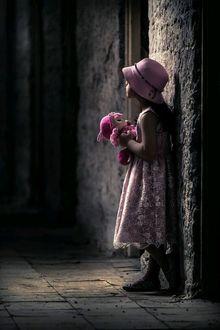 Фото Девочка с розовой куклой у стены дома