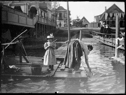 Фото Петербург начала 20 века, девочка в платье и женщина полощет в воде белье, фотограф Альфред Эберлинг