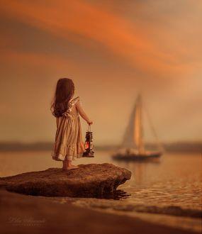 Фото Девочка с фонарем в руке стоит на берегу смотря на яхту в море, by Lilia Alvarado