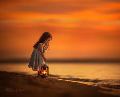 Фото Девочка с фонарем стоит у воды, ву Lilia Alvarado