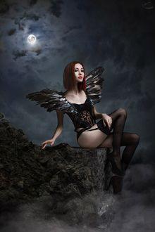 Фото Девушка в черном с крыльями сидит на камне на фоне луны, фотограф Александр Боцман