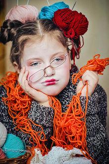 Фото Грустная девочка с мотками разноцветной пряжи, копирующая свою бабушку