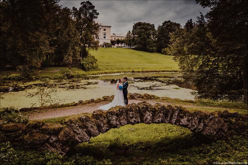 Фото Молодожены стоят на каменном мосту