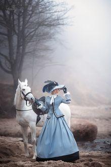 Фото Девушка в платье и в шляпе стоит с белым конем на песке около зера на фоне тумана, фотограф Ирина Недялкова
