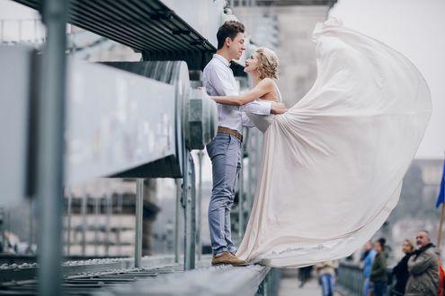 Фото Мужчина девушкой стоят на мосту обнимаясь, девушка взмахнула ногой, фотограф Олег Балюк