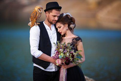 Фото Мужчина с девушкой обнимаются, девушка держит букет цветов, у мужчины на плече сидит сова, фотограф Илья Двояковский