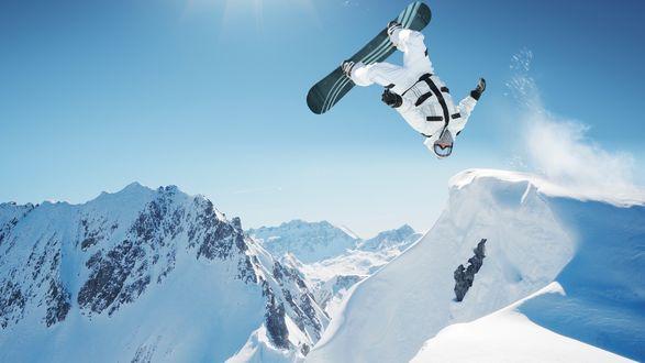 Фото Сноубордист в полете над заснеженной горой