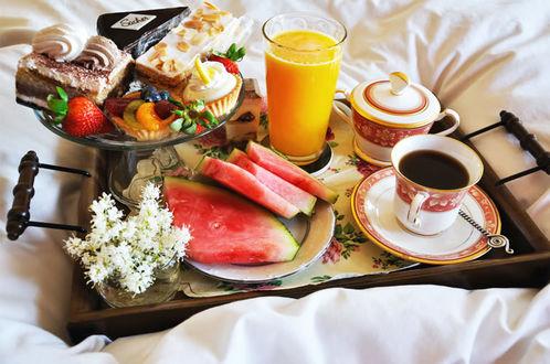 Фото Завтрак в постель, состоящий из кофе, апельсинового сока, арбуза, клубники, пирожных и белых цветов