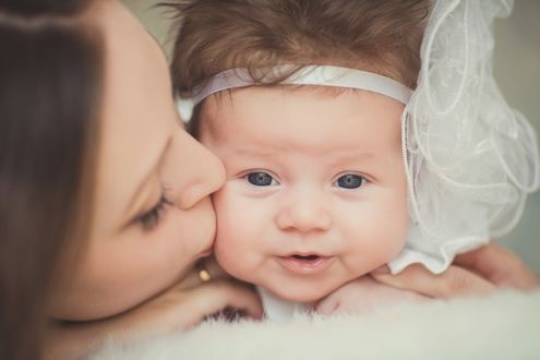 Фото Мама целует в щечку свою маленькую нарядную голубоглазую дочку