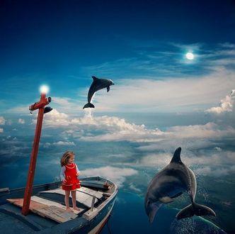 Фото Девочка стоит в лодке и смотрит на дельфинов, ву Caras Ionut
