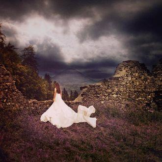 Фото Девушка в длинном белом платье стоит на фоне природы