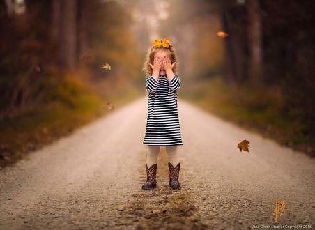Фото Девочка закрыла глаза руками, стоя на дороге в окружении летающих осенних листьев, by Jake Olson