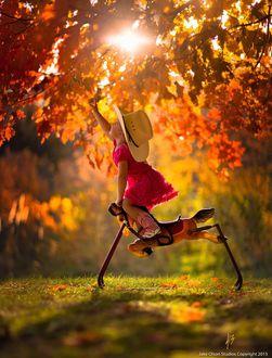 Фото Девочка сидя на игрушечной лошадке тянется к осенней листве дерева, by Jake Olson