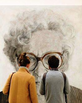 Фото Девушка и парень рассматривают баннер с пожилой женщиной в очках