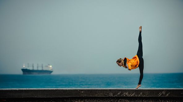 Фото Девушка в гимнастической позе стоит на фоне корабля в море, фотограф Баженов Денис