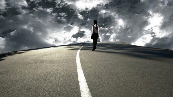 Фото Одинокая девушка с поникшими плечами, бредет по пустынному шоссе, постепенно исчезая вдали, на фоне хмурого неба