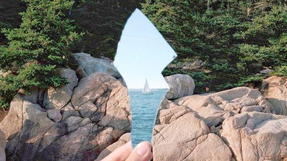 Фото Рука с зажатым осколком зеркала, в котором отражается море и парусная яхта, на фоне леса и валунов
