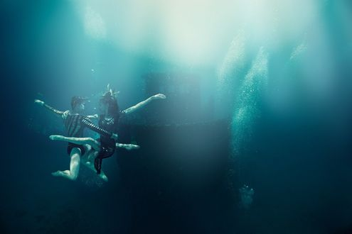 Фото Мужчина с девушкой под водой в танце около затонувшего корабля, by George Kamper