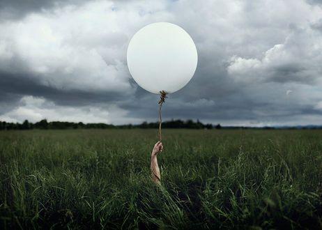 Фото Рука держит воздушный шар в поле на фоне облачного неба, by Talley