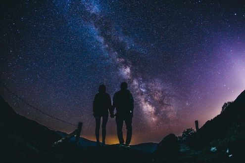 Фото Мужчина с девушкой держатся за руки на фоне Млечного пути