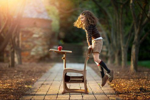 Фото Девочка в прыжке около стула и столика, на котором стоит яблоко, by Ashlyn Mae