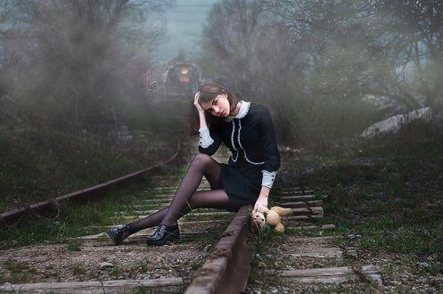 Фото Девушка с плюшевым медведем сидит на рельсах, сзади едет поезд, фотограф Алена Ленком