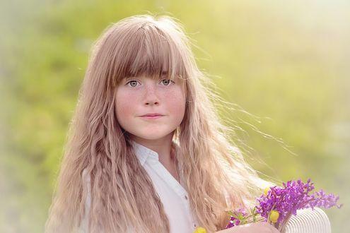 Фото Девочка с длинными волосами с полевыми цветами в руке
