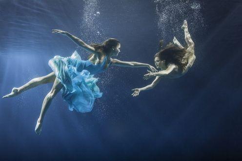 Фото Девушки танцующие под водой, на фоне воздушных пузырьков и сине-серой толщи воды. Фотограф Майя Алмейда / Maya Almeida