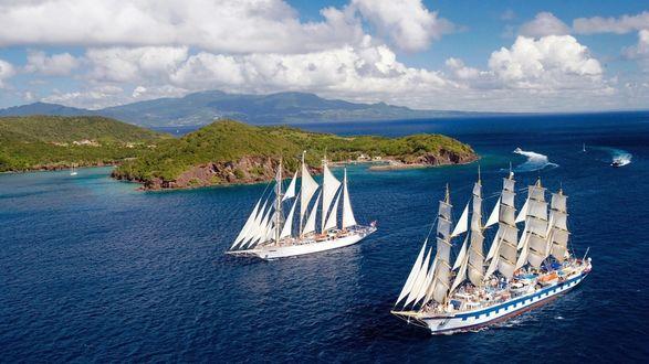 Фото Белоснежные парусники, разрезая синеву океана, проходят мимо поросших зеленью островов, под голубым небом с пушистыми облаками