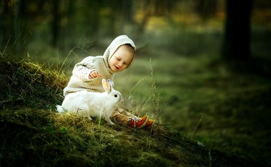 Фото Ребенок с кроликом сидит в траве, фотограф Олька Сергеева